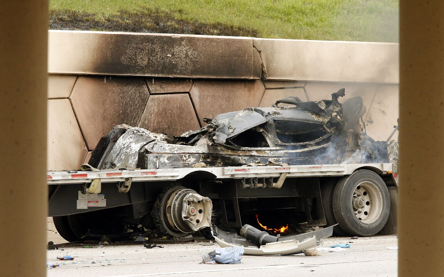 A burned out vehicle is pinned against the wall by a semi truck after it crashed following a high speed chase on Interstate-30 near Cooper St. in Arlington  Friday, June 9, 2017. The driver of the vehicle escpaed before the car burned.