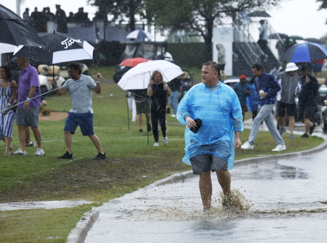 A fan makes their way through a puddle as others walk around as rain continues to fall during round 4 of the AT&T Byron Nelson  at TPC Craig Ranch on Saturday, May 16, 2021 in McKinney, Texas. (Vernon Bryant/The Dallas Morning News)