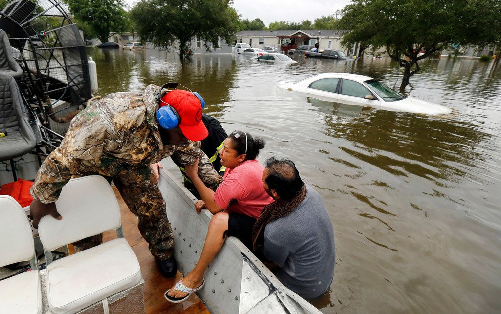 Gulf Coast Rescue Squad air boat driver Felton Jones (left) pulls LaJuana Cinseros into the boat with the assistance of her husband Freddie Cisneros as they were rescued from their flooded home in Pearland Acres Mobile Home Community in rural Pearland, Texas, Sunday, August 27, 2017. Tropical Storm Harvey dumped several feet of rain along the southeast Texas coast and the Houston area.