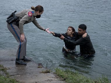 A Texas Department of Public safety trooper helps Belkis Salas of Venezuela out of the Rio Grande near Del Rio on Friday, April 30, 2021. Salas struggled to cross the river, falling halfway through and being pulled up by her son-in-law and a smuggler. Many Venezuelans are being welcomed for asylum processing on one part of the border while Central Americans are being quickly expelled on other parts of the border.