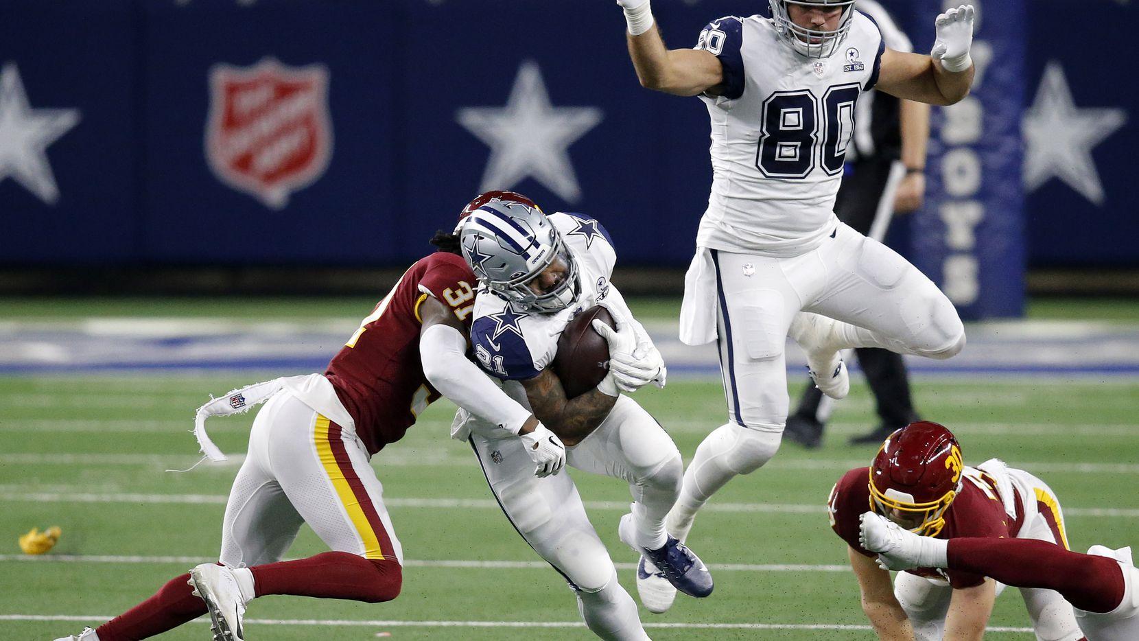 Cowboys running back Ezekiel Elliott (21) is wrapped up by Washington safety Kamren Curl (31) during a third-quarter run at AT&T Stadium in Arlington on Thursday, Nov. 26, 2020.