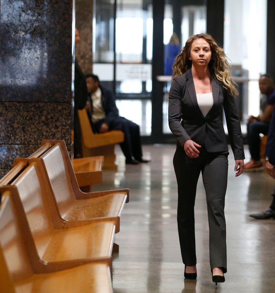 Former Dallas police Officer Amber Guyger (left) walks the hallway at the Frank Crowley Courts Building in Dallas. Guyger is charged with murder in the Sept. 6 shooting death of Botham Jean in his apartment.