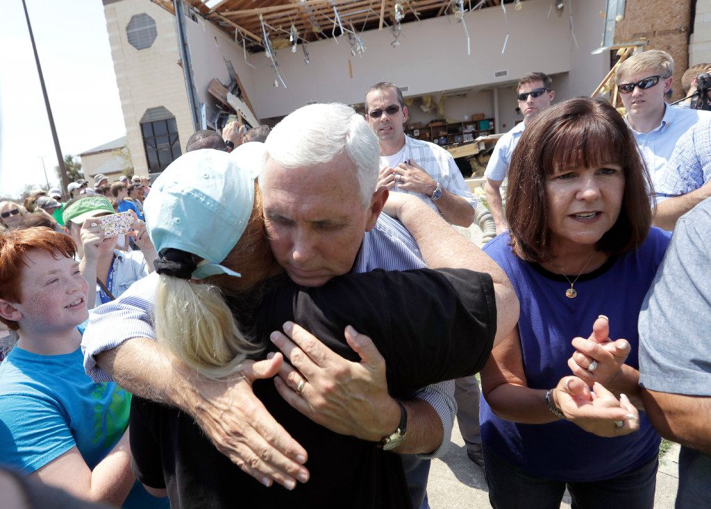 Vice President Mike Pence, with his wife Karen by his side, shares a hug as he tries to encourage residents affected by Hurricane Harvey during Thursday's visit.