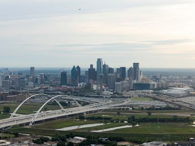 Margaret McDermott Bridge, bottom, seen crossing the Trinity River on I-30 as the sunrises behind the Dallas skyline on Friday, June 14.