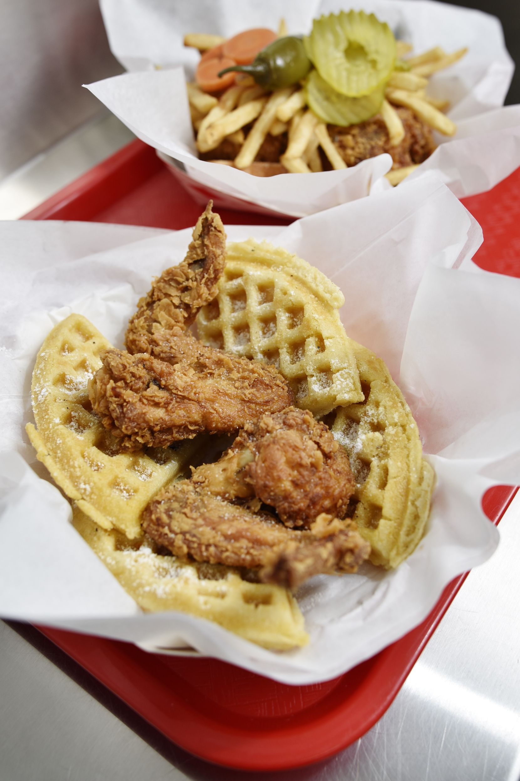 Hall's Honey Fried Chicken offers baskets of two-piece chicken and waffles and two-piece chicken served with fries, pickles and two pieces of white bread.