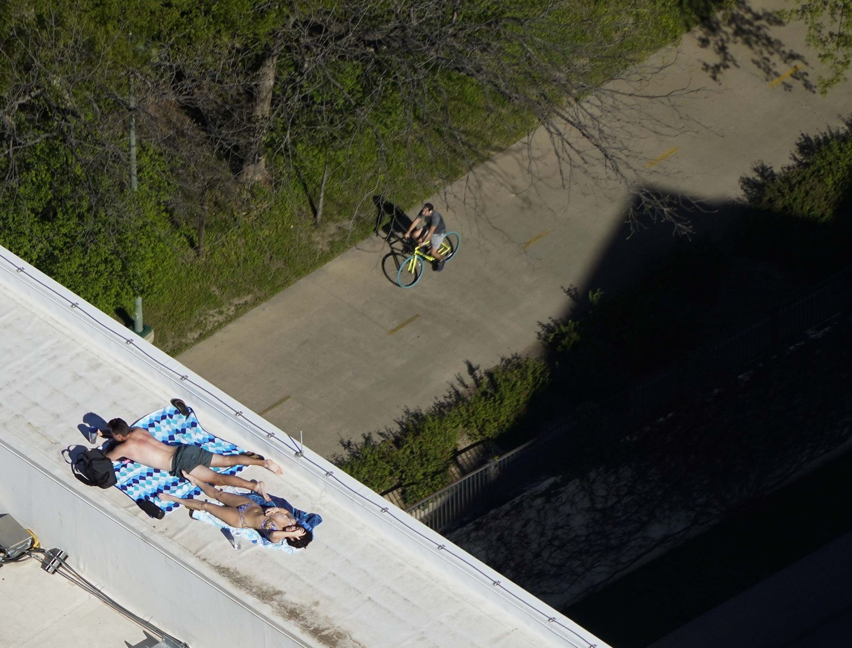 A couple sunbathes on the roof of the The Katy in Victory Park Apartments as a man rides by on a bike on Tuesday, March 24, 2020 in Dallas.