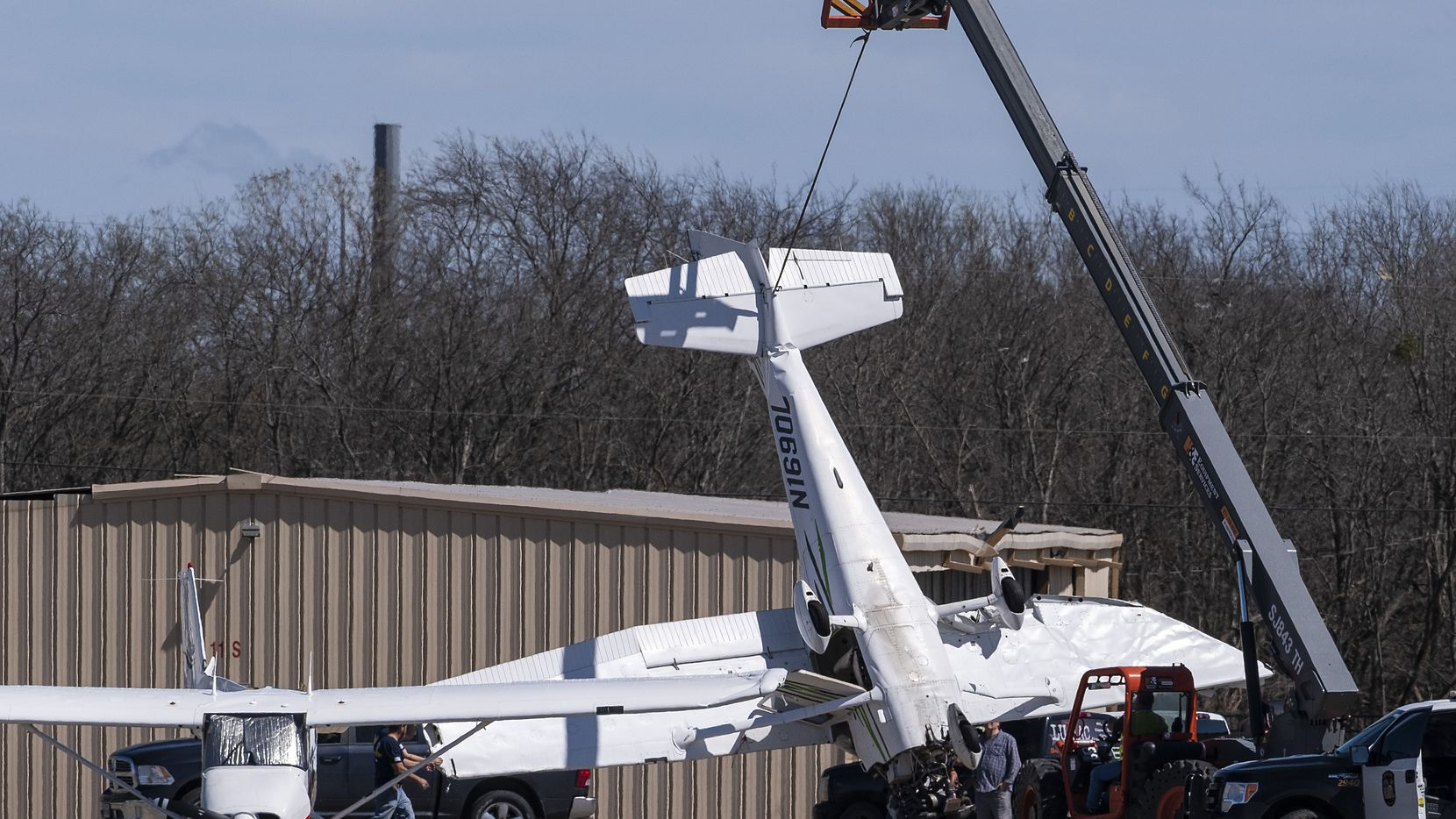 Workers used a crane to clear aircraft that storms early Wednesday damaged at Grand Prairie Municipal Airport in Grand Prairie.