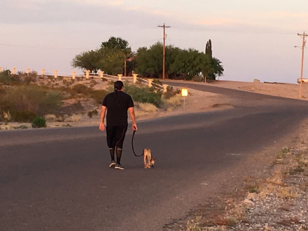 A man walks his dog at sunset along a quiet road in Presido, a tiny Texas town that borders Ojinaga, Chihuahua, which is five times larger.
