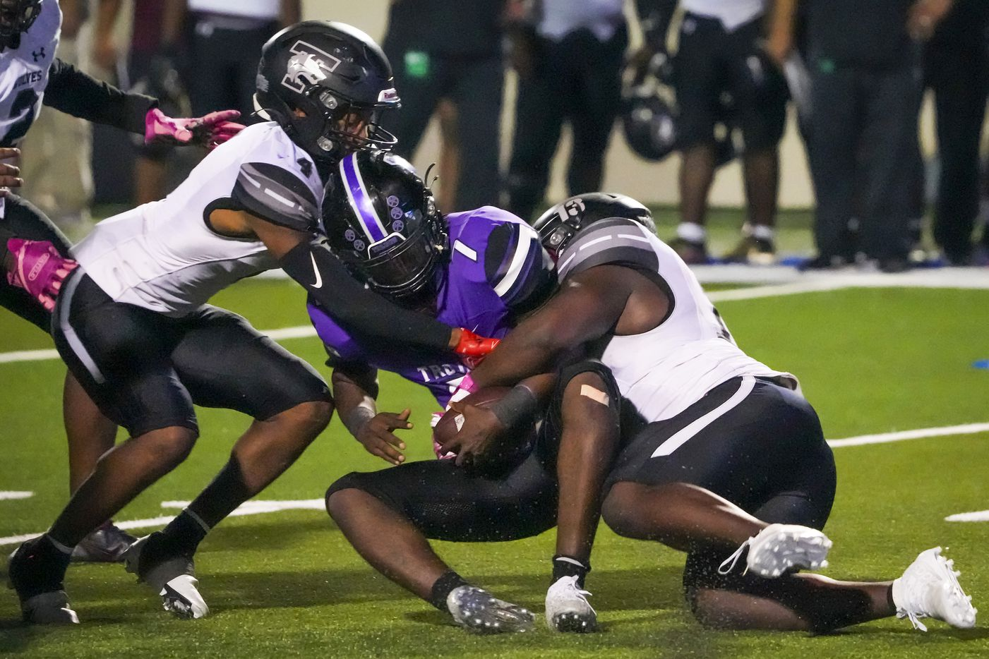 Waco University quarterback Damarion Chambers (7) is dropped for a loss by Mansfield Timberview's Kye Nash (13) and Jonathan Smith (4) during the first half of a high school football game at Waco ISD Stadium on Friday, Oct. 8, 2021, in Waco, Texas.