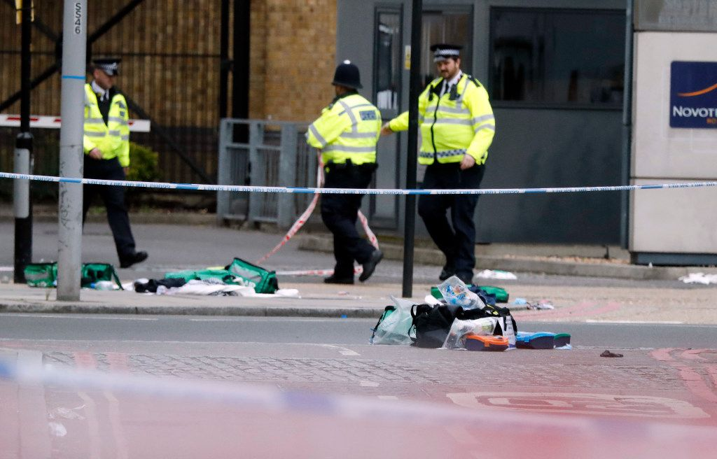 Police patrol nears bags of evidence collected on the streets in the London Bridge area of London, Sunday, June 4, 2017.