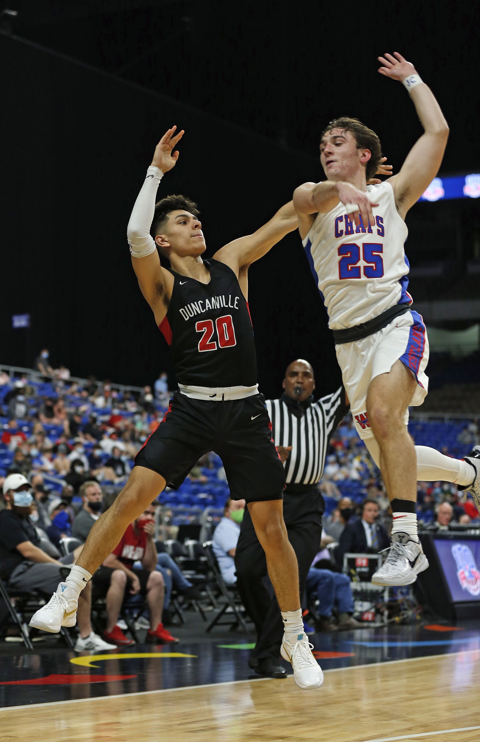 Duncanville Juan Reyna #20 makes a three despite pressure from Westlake Eain Mowat #25. UIL boys Class 6A basketball state championship game between Duncanville and Austin Westlake on Saturday, March 13, 2021 at the Alamodome.