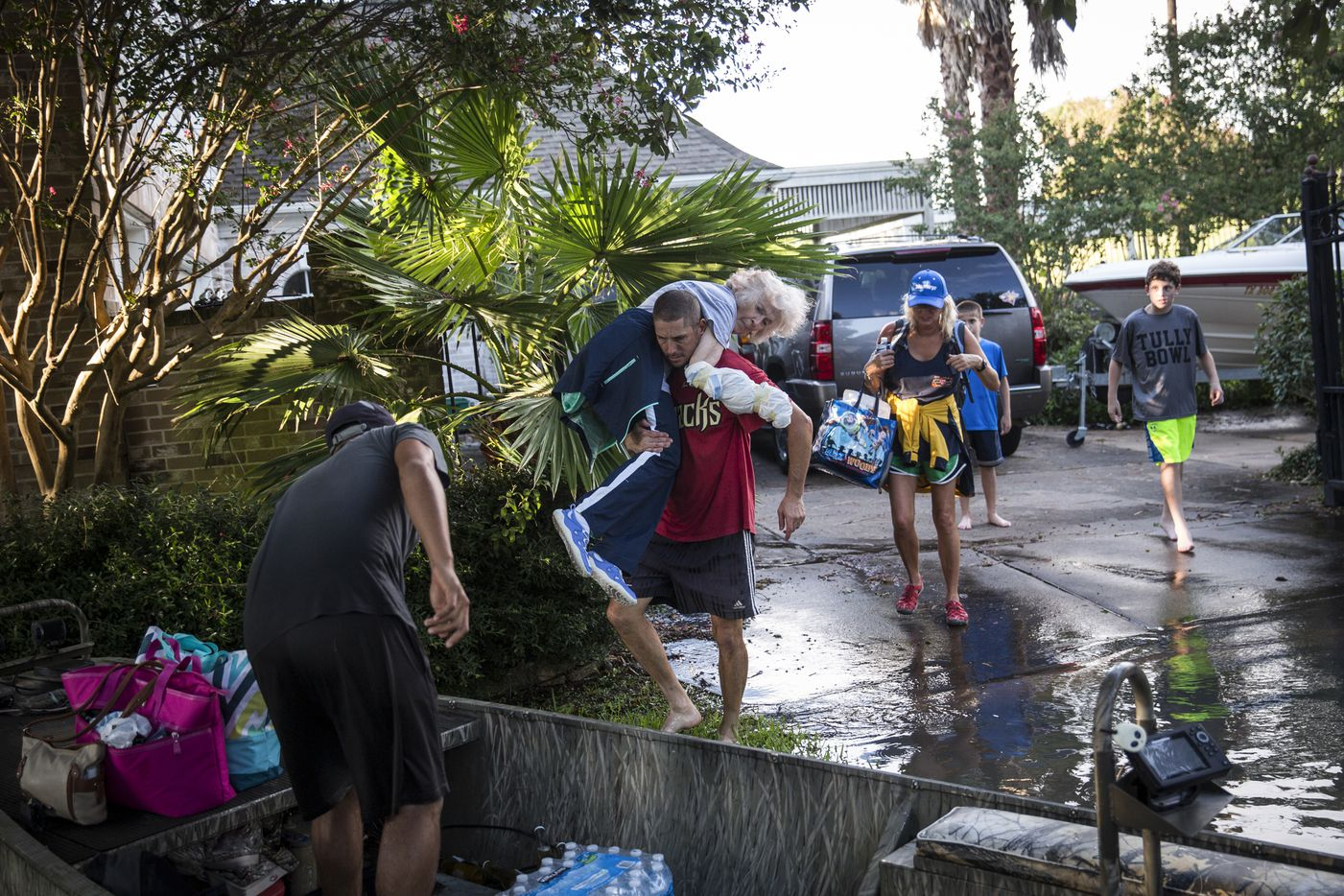 Louis Goode is carried to a boat by her son-in-law, John Zarnowiecki, during a search and rescue operation in Houston, Aug. 29, 2017.
