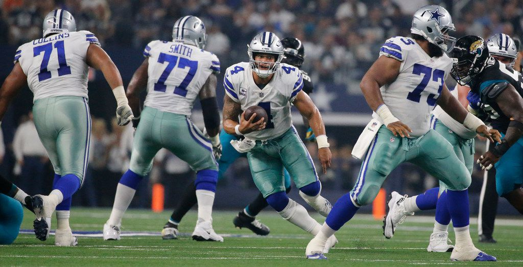 Dallas Cowboys quarterback Dak Prescott (4) rolls out of the pocket behind blocking by Dallas Cowboys offensive linemen La'el Collins (71), Tyron Smith (77) and Joe Looney (73) during the Jacksonville Jaguars vs. the Dallas Cowboys NFL football game at AT&T Stadium in Arlington, Texas on Sunday, October 14, 2018. (Louis DeLuca/The Dallas Morning News)