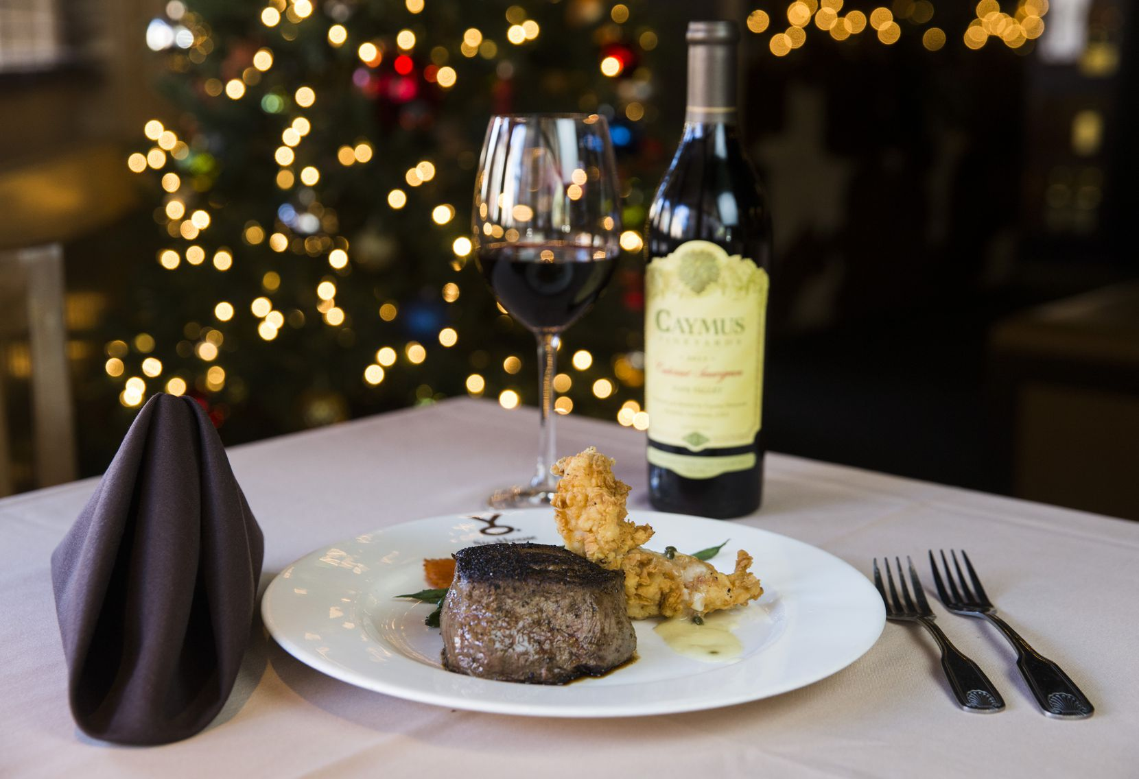 Petite filet and chicken fried lobster paired with a glass of Caymus Vineyards Cabernet Sauvignon as part of Y.O. Ranch Steakhouse's New Year's Eve menu, as photographed on Tuesday, December 17, 2019 in Dallas. (Ashley Landis/The Dallas Morning News)