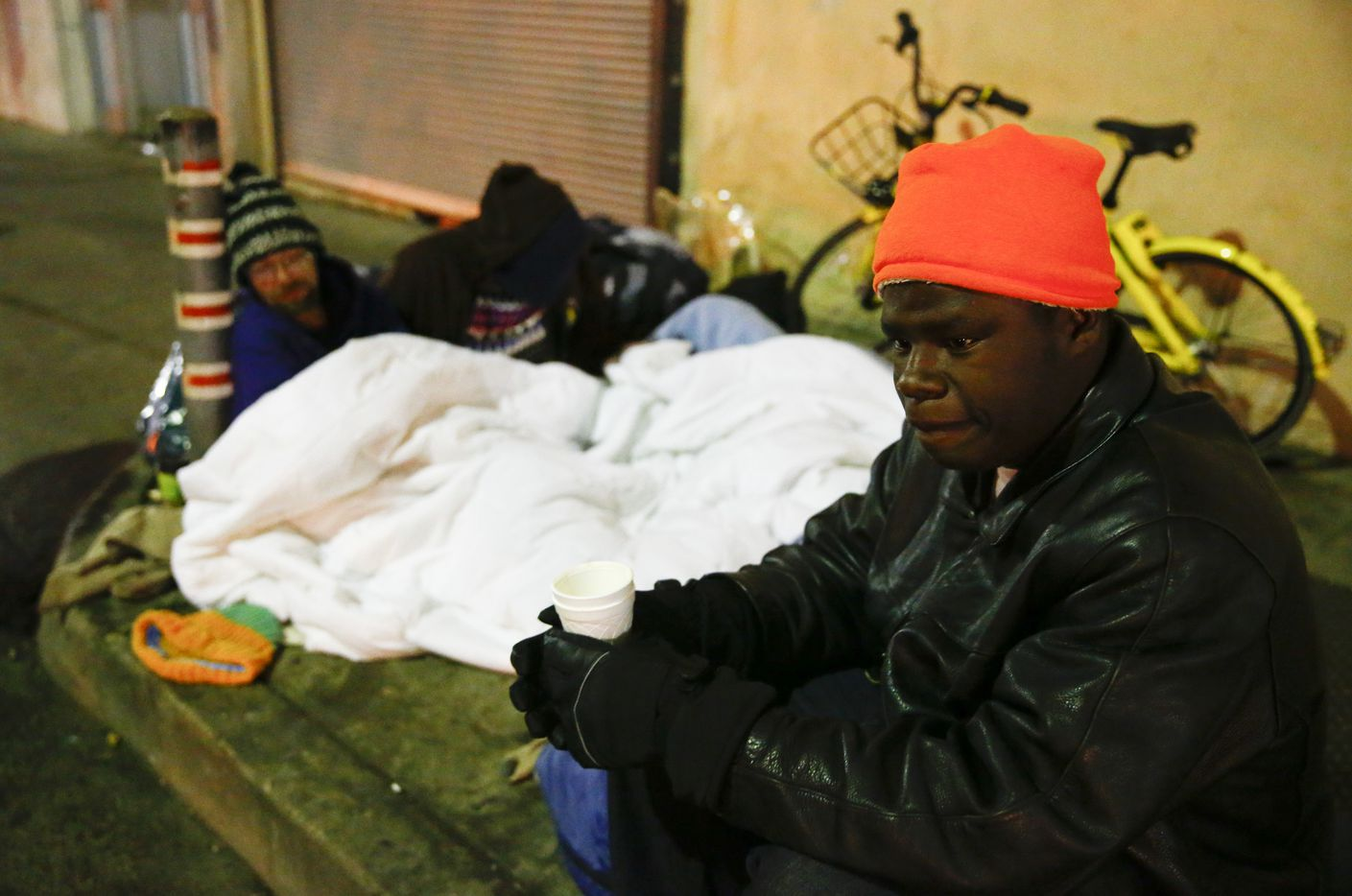 Dawaylon Raymond, 20, (right) drinks some donated coffee as Ryan Rule, 39, (left) and his wife, Deshonda Rule, 33, sleep on top of an exhaust vent next to The Stewpot on Park Ave in downtown Dallas on Jan. 16, 2018. Temperatures sunk into the teens throughout the night.  (Nathan Hunsinger/The Dallas Morning News)