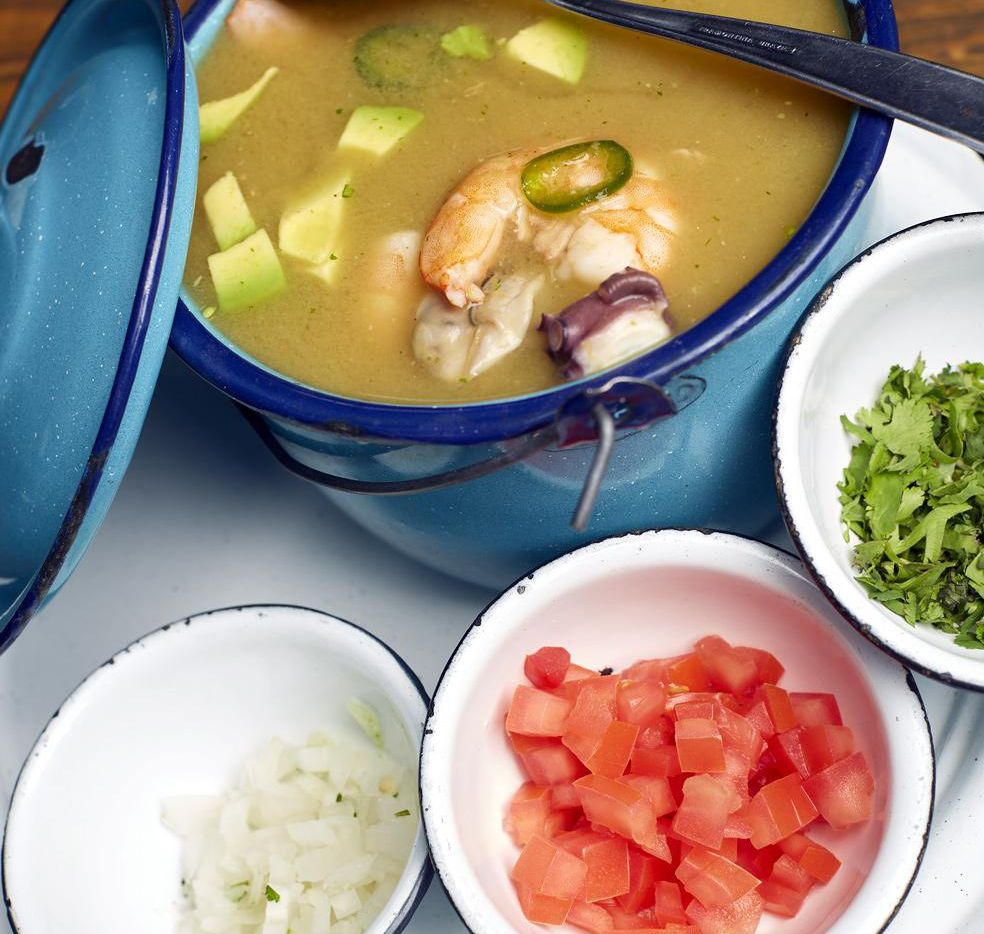 Caldo de mariscos con camarón, pulpo y ostiones, acompañado de tomate y cebolla