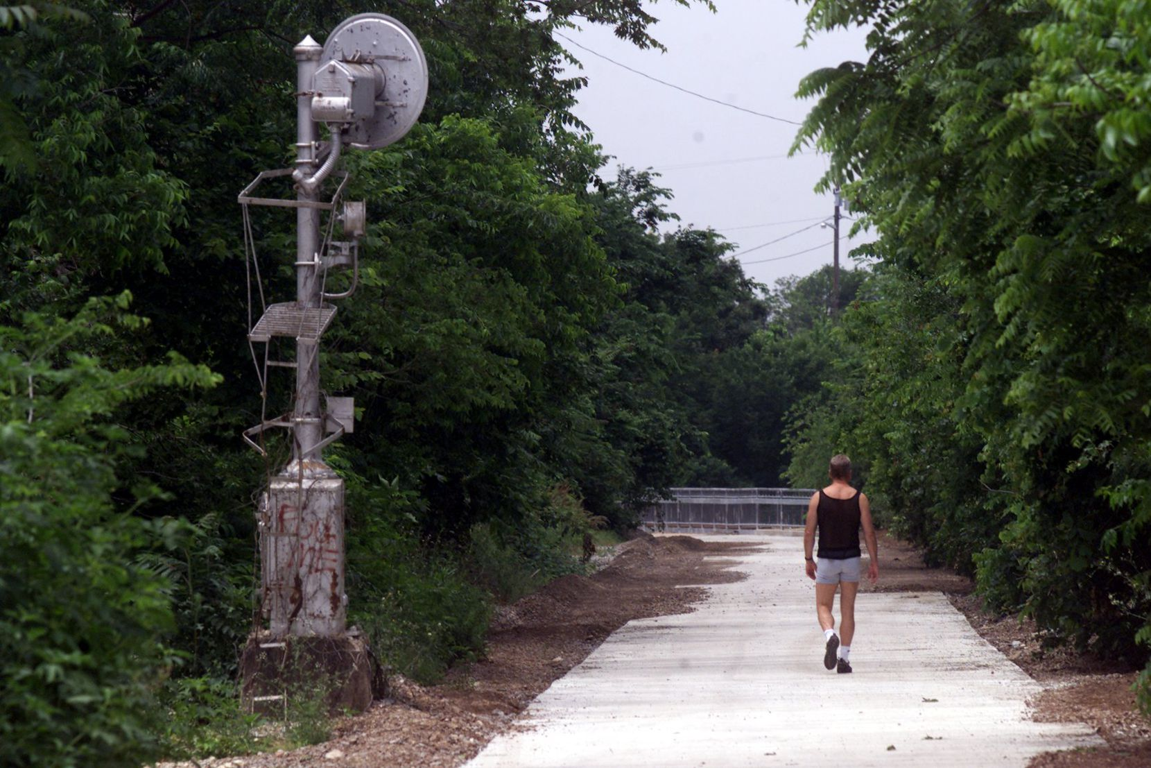 The old Katy railroad tracks were turned into an urban bike/hike trail. In this photo near Reverchon Park you can still see an old railroad signal as a man walks down the trail on May 10, 2000.
