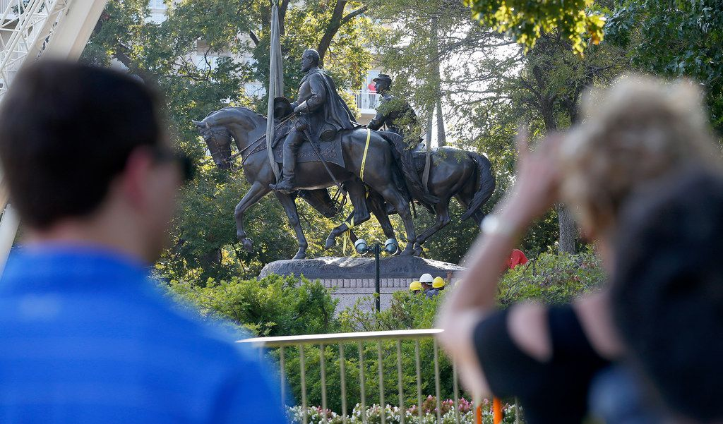 People watch crew members work to remove the Robert E. Lee statue at Robert E. Lee Park in Dallas, Thursday, Sept. 14, 2017.