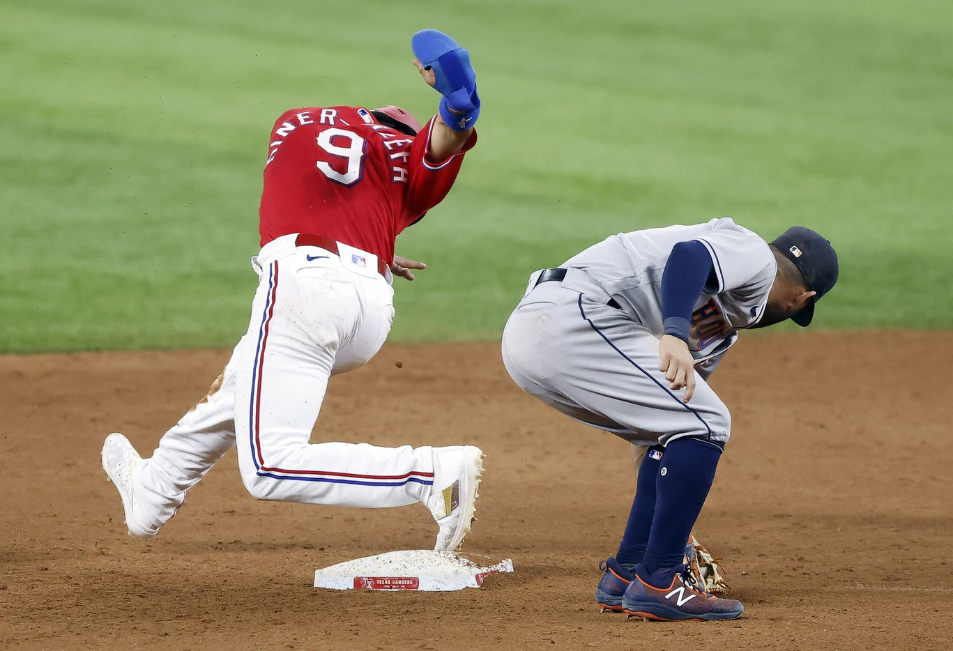 Texas Rangers shortstop Isiah Kiner-Falefa (9) slides safely past Houston Astros second baseman Jose Altuve (27) on a stolen base attempt in the ninth inning at Globe Life Field in Arlington, Texas, Friday, May 21, 2021. The play was reviewed and called safe. (Tom Fox/The Dallas Morning News)
