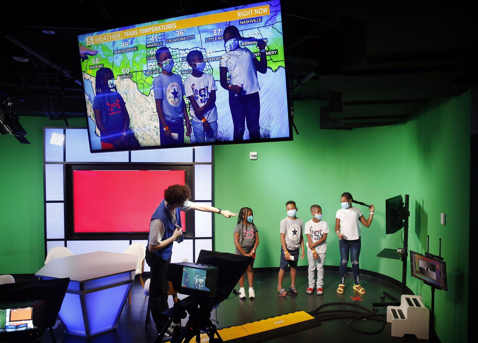 Los niños se paran frente a una pantalla verde mientras entregan pronósticos del tiempo en el estudio de televisión para niños WFAA en KidZania Dallas, la única ubicación de la compañía en los EE. UU. En Stonebriar Mall en The Bridges en Plano, Texas, el 16 de julio de 2021 (Tom Fox / The Dallas Morning News)