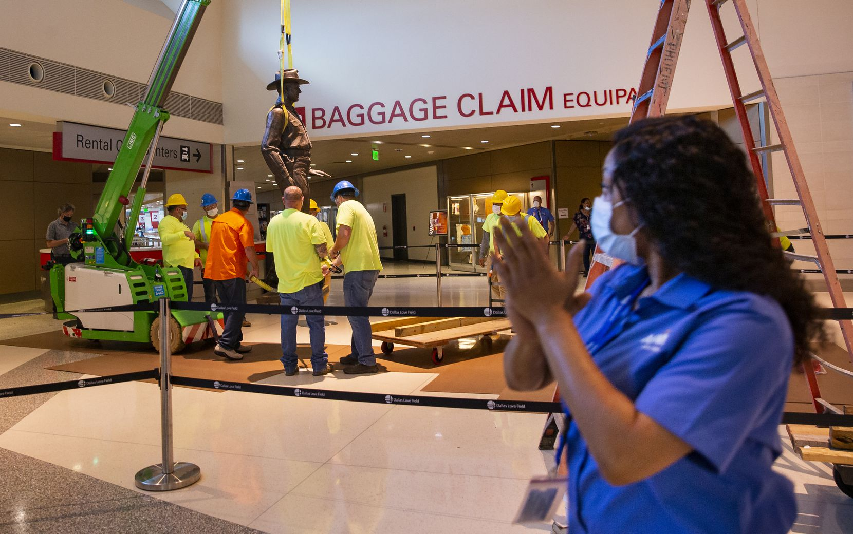 "Tiffany Anderson claps as a Phoenix 1 Restoration & Construction crew removes 'One Riot, One Ranger' from the main lobby inside Love Field airport on Thursday, June 4. ""He's racist, he's got to go,"" Anderson said."