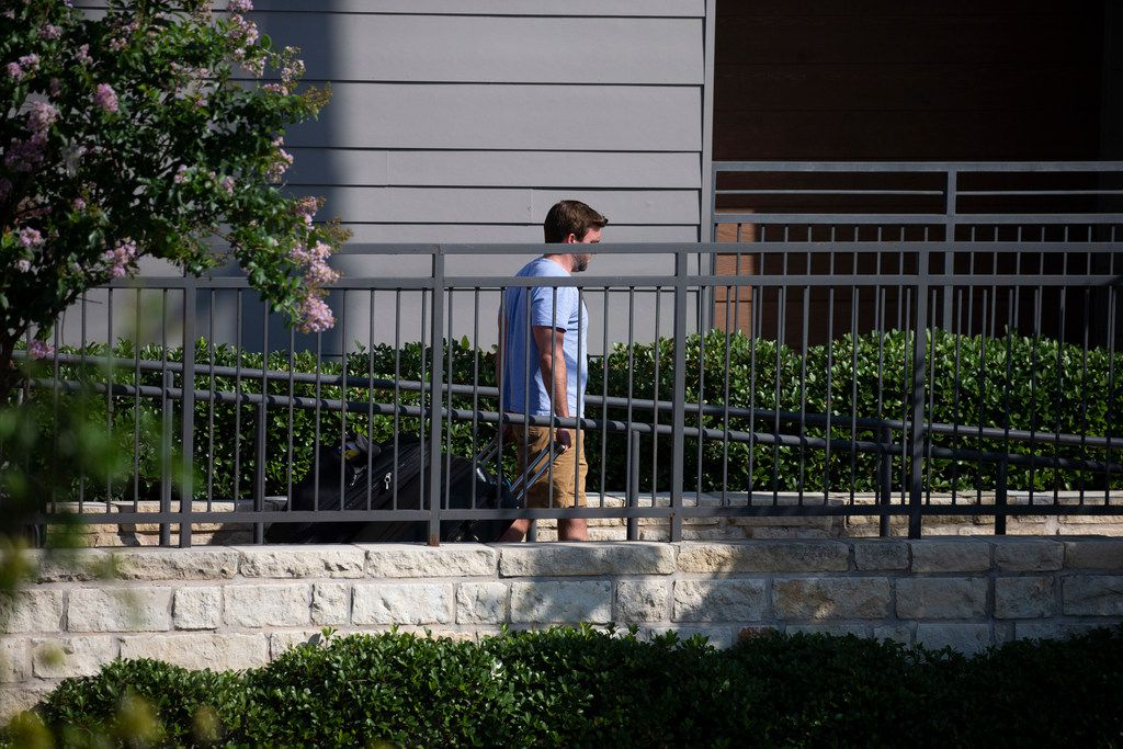 A resident exits Elan City Lights apartments with a couple of bags in Dallas.