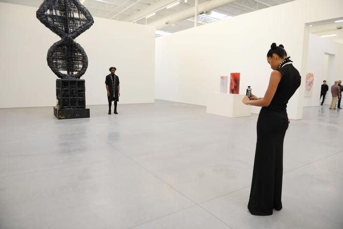 """Erika Oliver takes a photo of Charles Smith II next to """"Elliptic Umbilic/Fait Accompli"""" by Sterling Ruby during a public tour at The Warehouse."""