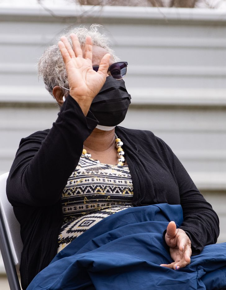 Marsha Jackson raises her hand while listening to opera singer Lawrence Brownlee perform outside of her home in Dallas on Friday, Feb. 26, 2021. Quincy Roberts, the contractor who moved Shingle Mountain, surprised Jackson with the concert. (Juan Figueroa/ The Dallas Morning News)