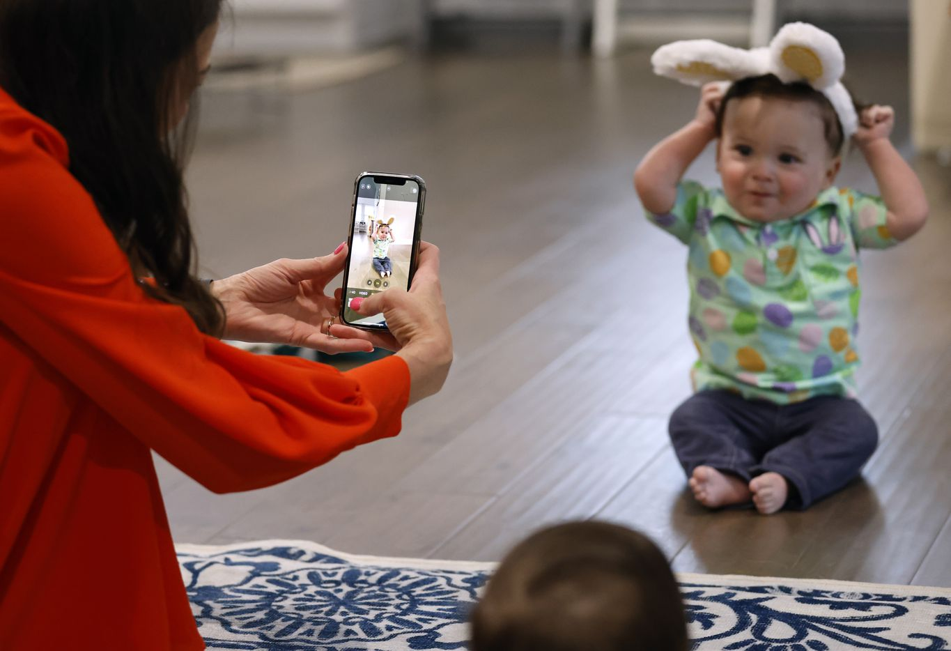 Jenny Marr takes a photo of Hudson Marr with bunny ears on after they went through items received in their Easter basket at their home on Sunday, April 4, 2021 in Grapevine, Texas.