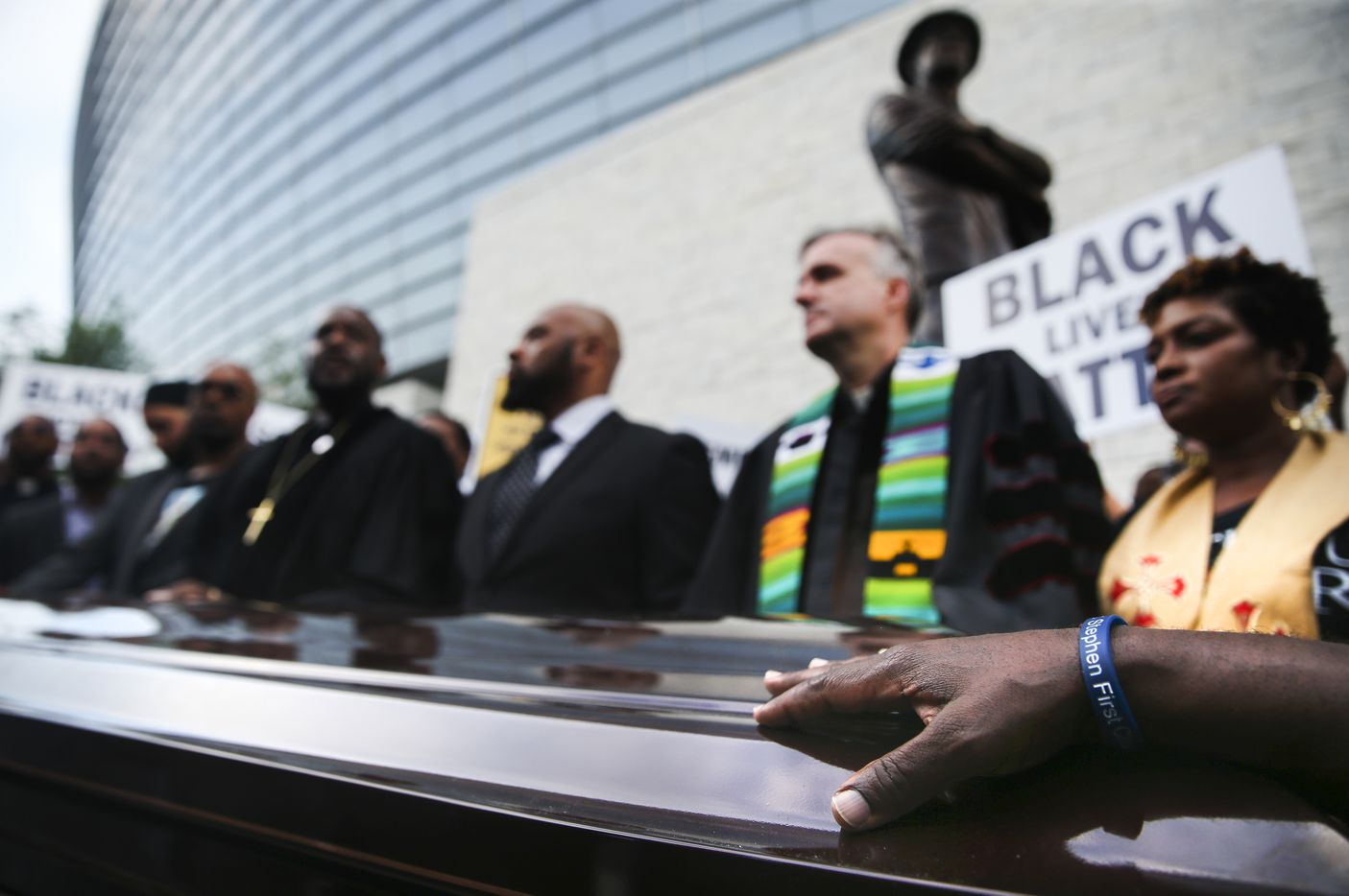 Members of the clergy and community place their hands upon two empty coffins symbolizing the double-murder of black victims' bodies and their names during the protest.