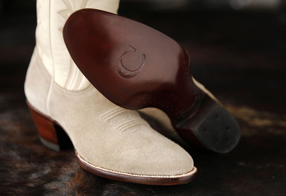 """A distinctive """"C"""" is engraved in the leather sole of her boots."""