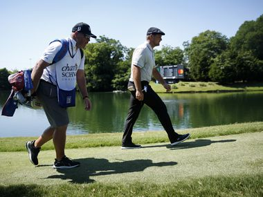 PGA Tour golfer Bryson DeChambeau and his caddie Tim Tucker walk back up the par-3, No. 13 during his third round of the Charles Schwab Challenge at the Colonial Country Club in Fort Worth, Saturday, June 13, 2020.