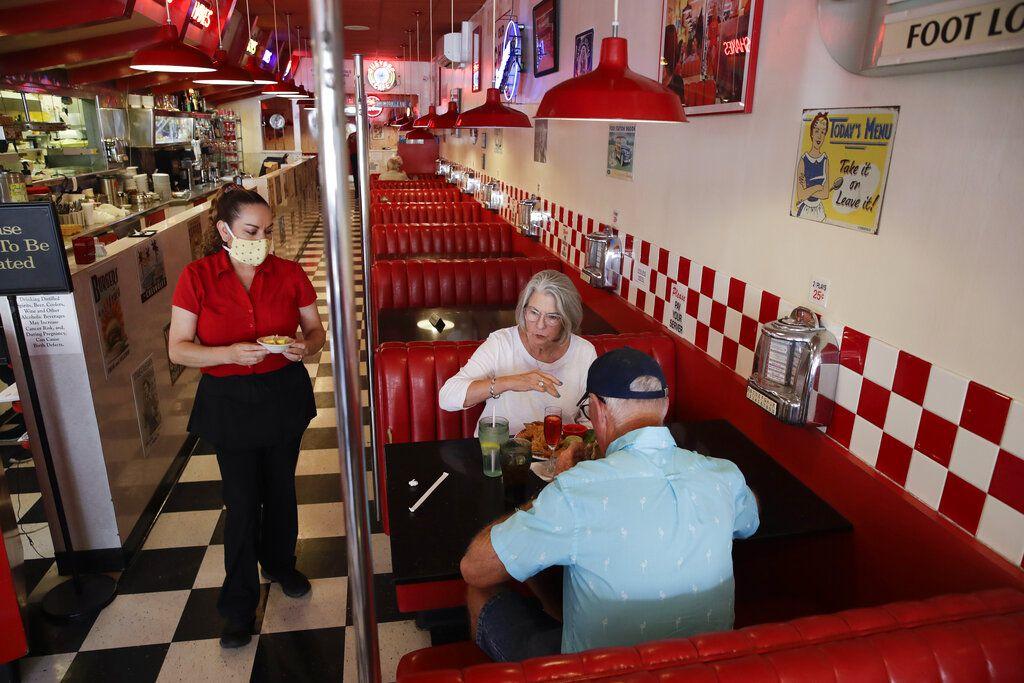Lynn Tanner (al centro) y su esposo Ryan (derecha) almuerzan en el restaurante Busy Bee Cafe el jueves 21 de mayo de 2020, en Ventura, California. Es poco probable que la mayoría de los estadounidenses regrese pronto a los restaurantes, bares, teatros o gimnasios, a pesar de que las autoridades estatales y locales de todo el país permitan cada vez más la reapertura de negocios, según una nueva encuesta realizada por The Associated Press-NORC Center for Public Affairs Research.
