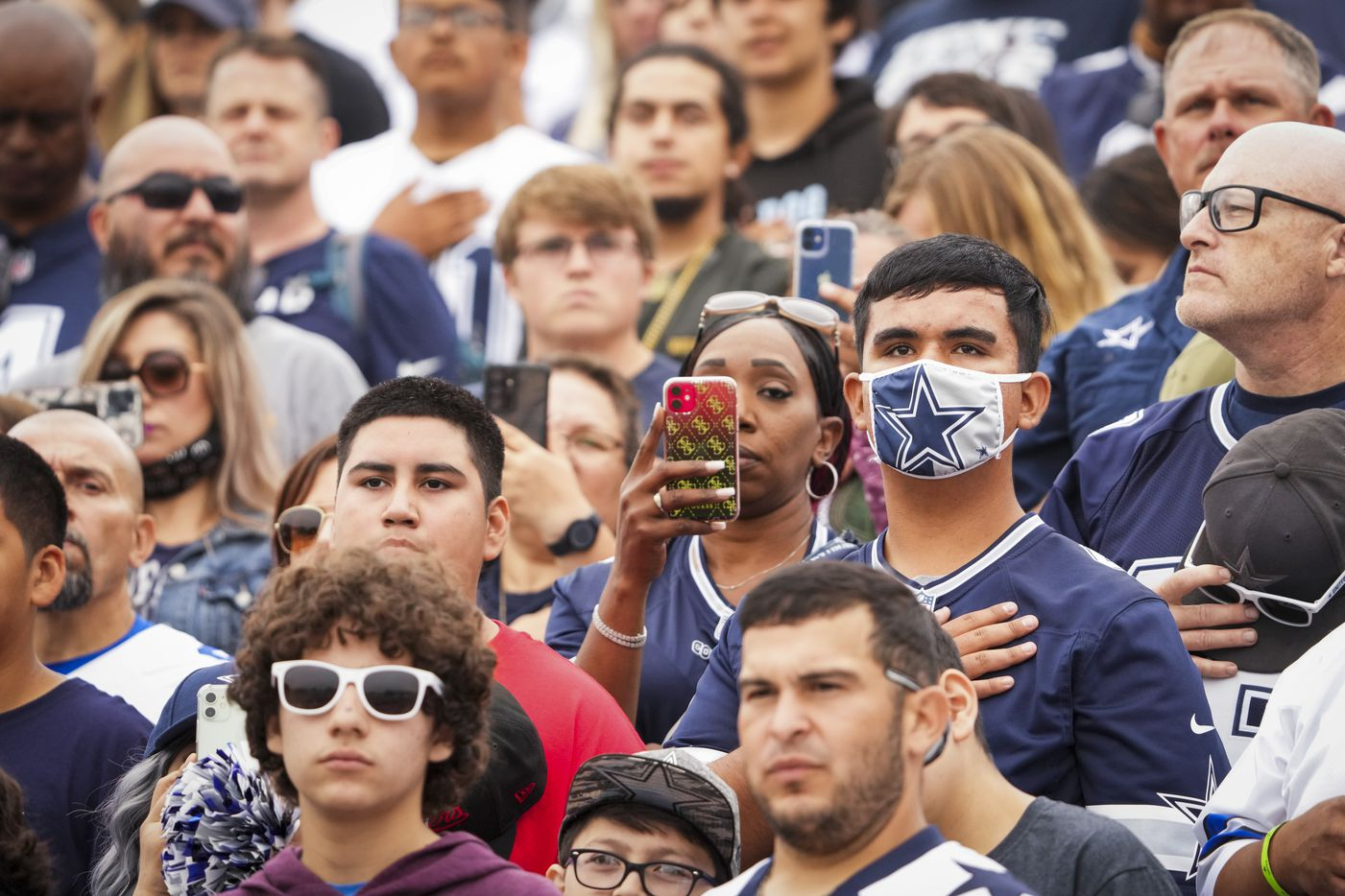 Fans stand for the national anthem during the Dallas Cowboys opening ceremonies before a practice at training camp on Saturday, July 24, 2021, in Oxnard, Calif.