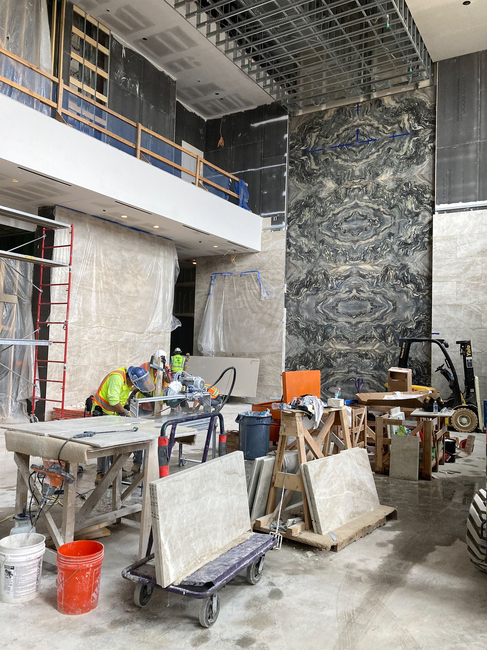 Work crews install stone on the walls of the office lobby in the Weir's Plaza tower. The first tenants are expected to take occupancy in early 2022.