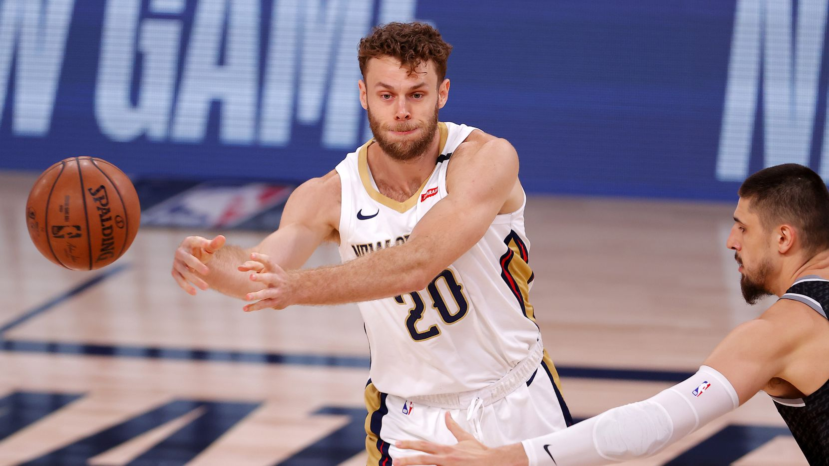 Nicolo Melli, left, of the New Orleans Pelicans passes the ball during the first quarter of an NBA basketball game Tuesday, Aug. 11, 2020, in Lake Buena Vista, Fla.
