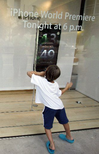 A youngster watches the countdown clock as he and others wait in line outside the Apple Store on Knox Street to buy the original iPhone on July 29, 2007.