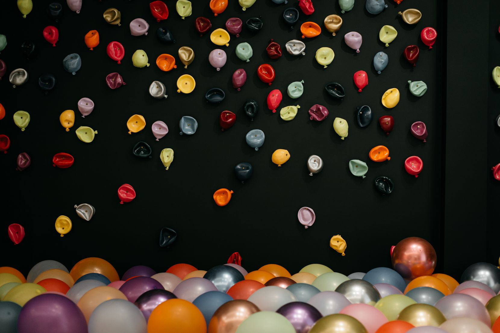 "Jessica Bell's ""300 Balloons"" features a wall covered with colorful balloon sculptures. Real balloons sit on the ground in front of the wall, ready to be used as props for Instagram shots."