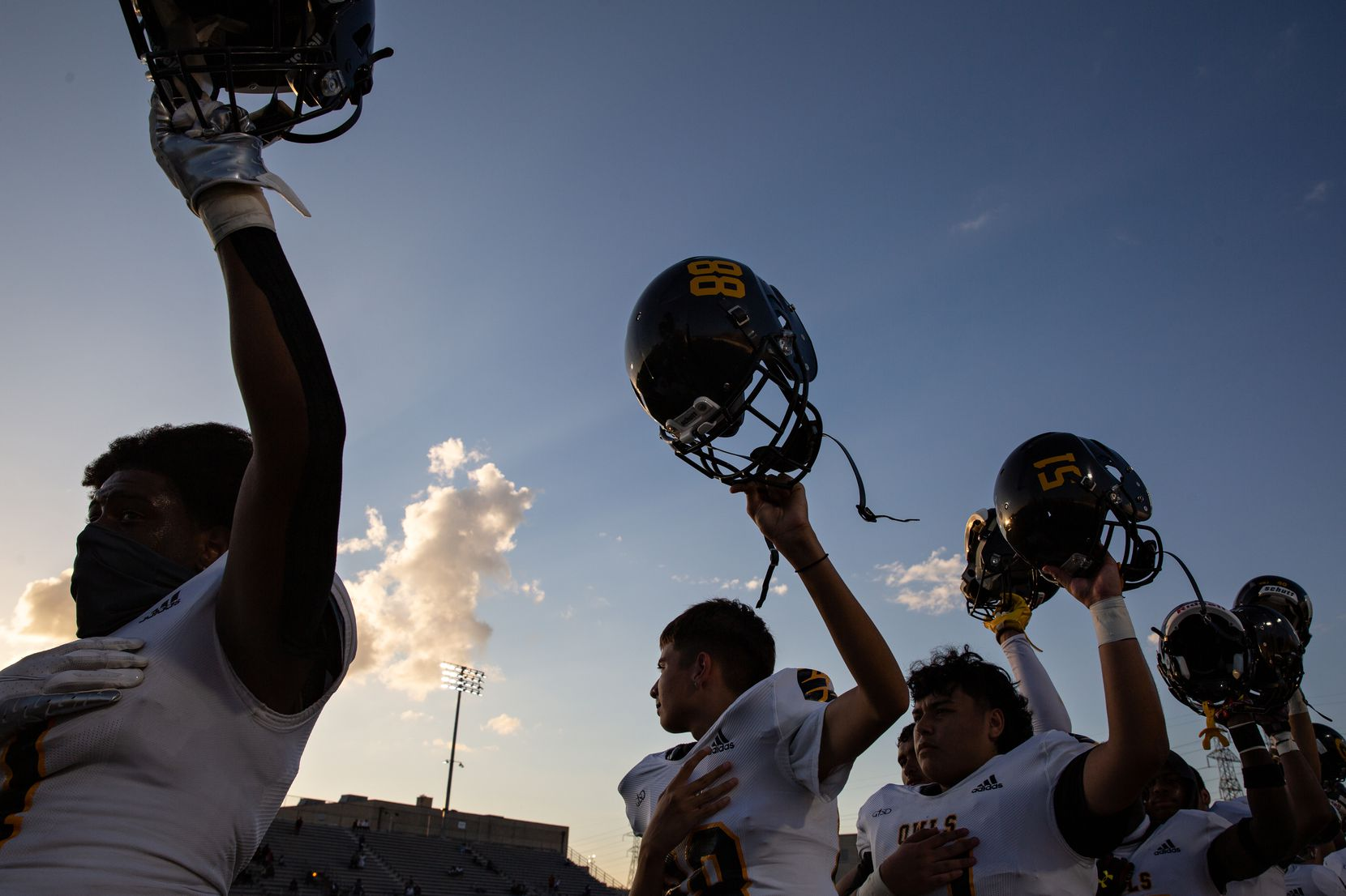 Garland High School football players put their helmets in the air during the Star Spangled Banner before the season-opening game at Sprague stadium against Justin F. Kimball High School on August 27, 2021.  (Shelby Tauber/Special Contributor)