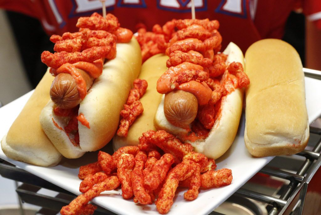 The Flamin'' Hot Cheetos Dog is an all beef hot dog topped with Flamin'' Hot Cheetos infused nacho cheese and sprinkled with Flamin'' Hot Cheetos. Located in sections 22 and 48.