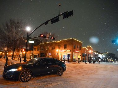 Cars move slowly through Historic Downtown Plano as a second winter storm brought more snow and continued freezing temperatures to North Texas on Tuesday night.