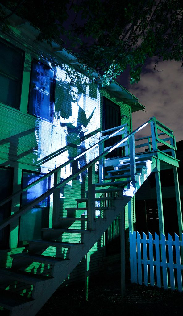 A famous 1963 photo of Lee Harvey Oswald holding a rifle is projected onto the back of the house where it was taken, at 214 W. Neely St. in Dallas, where Oswald lived in 1963. The scene is shown Wednesday, Aug. 8, 2018. Marina Oswald said she took the original photo at Oswald's request as he held a 6.5 mm Mannlicher-Carcano model rifle and wore a Smith & Wesson revolver. The same model rifle was found in the Texas School Book Depository after President John F. Kennedy was shot and killed 8 months later.