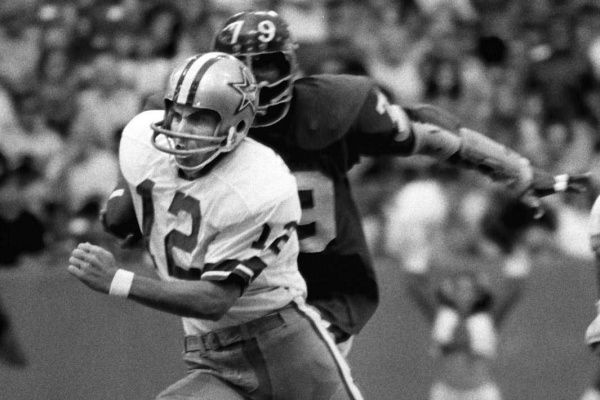 Roger Staubach (12) scrambles from a New York Giants defender during a game played on Oct. 21, 1973 at Texas Stadium.