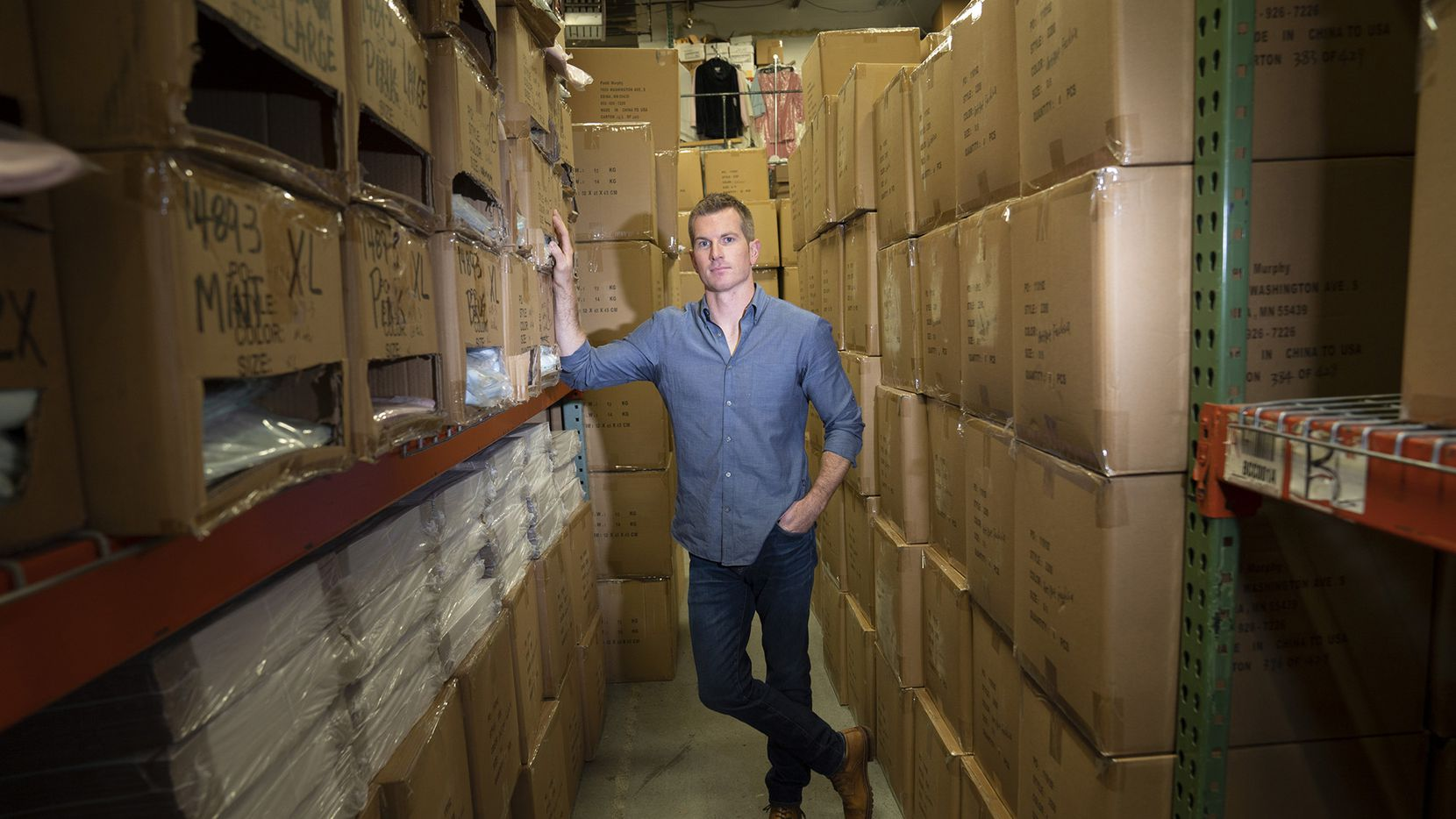 Tim Murphy, president of Softies, poses for a photo among stacked boxes in the company's Edina warehouse.