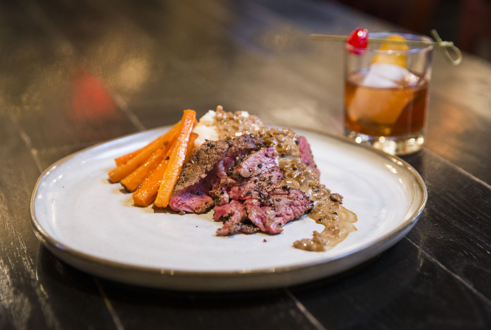 Beef tenderloin au poivre with blue cheese mash paired with a Kooper Family Rye Old Fashioned as part of The Holy Grail Pub's five-course New Year's Eve five course pairing menu, as photographed on Tuesday, December 17, 2019 in Plano. (Ashley Landis/The Dallas Morning News)