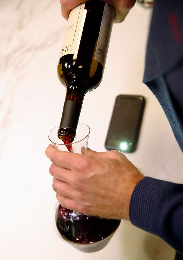James Tidwell demonstrates how he uses the light on his smartphone while pouring wine into a decanter.