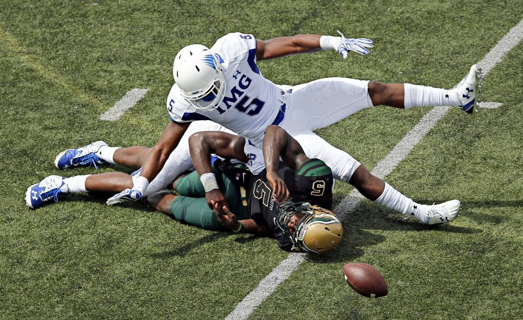 DeSoto's quarterback Tristen Wallace (5) fumbles the ball as he is brought down by IMG defenders Rahshaun Smith (top) and Joshua Kaindoh during the first half of their game Saturday, September 5, 2015 at Eagle Stadium in DeSoto, Texas. (G.J. McCarthy/The Dallas Morning News)