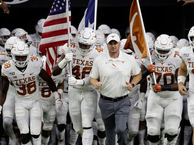 Texas head coach Tom Herman, center, takes the field with his team before the Longhorns' game against Rice Saturday, Sept. 14, 2019, in Houston.
