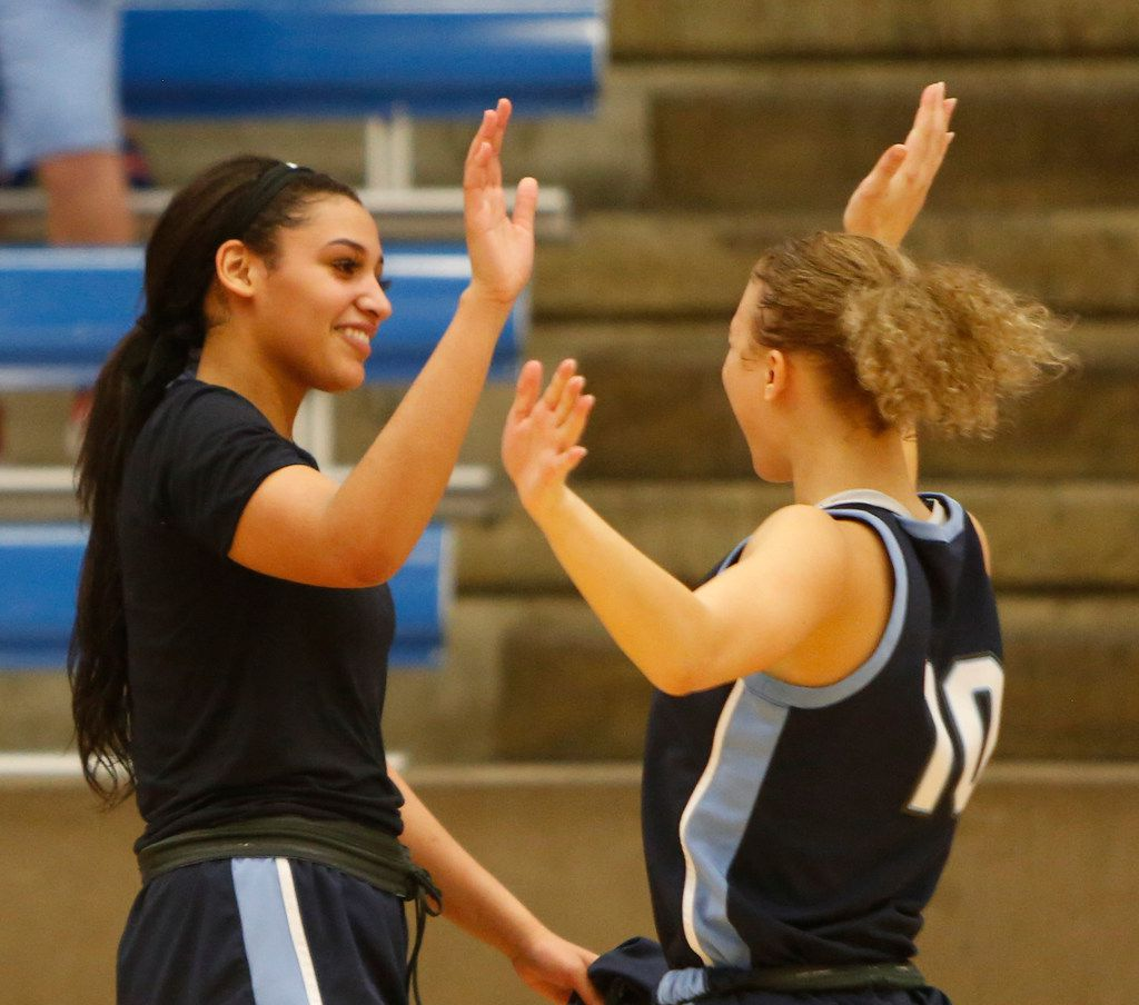 Hurst L.D. Bell guards Myra Gordon (15), left, shares a high five with Jaidyn Carter (10) following their 82-53 victory over Arlington Bowie to advance. The two teams played their Class 6A bi-district girls basketball game at Grand Prairie High in Grand Prairie on February 17, 2020. (Steve Hamm/Special Contributor).