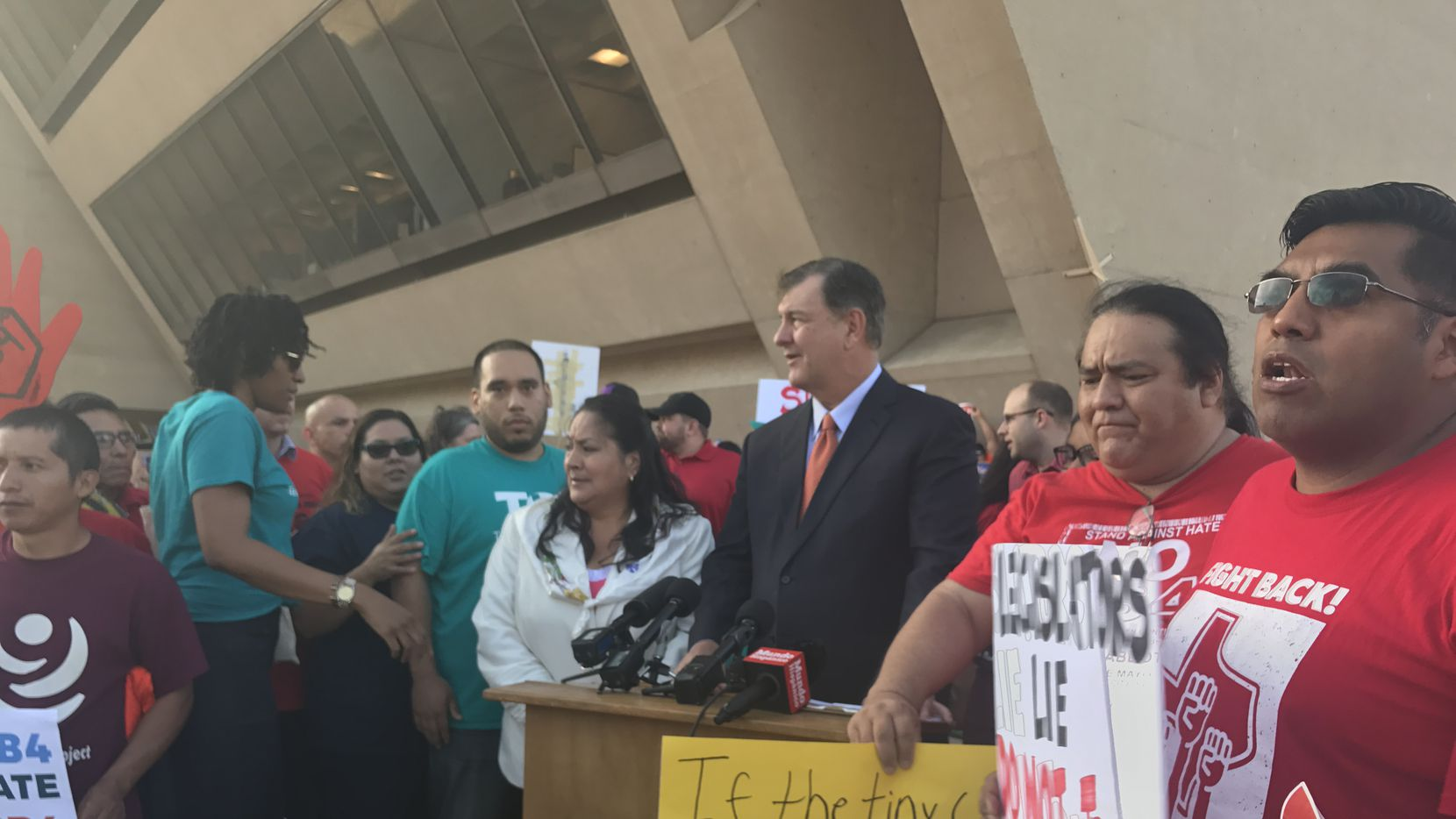 Dallas Mayor Mike Rawlings with protesters Wednesday morning outside Dallas City Hall. The group gathered to urge city officials to fight the state's new Sanctuary Cities law.